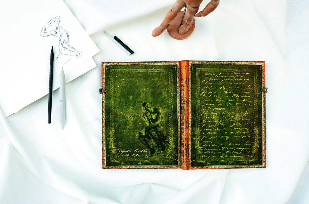 Paperblanks Rodin Journal open flat with pens and an artist wood figure